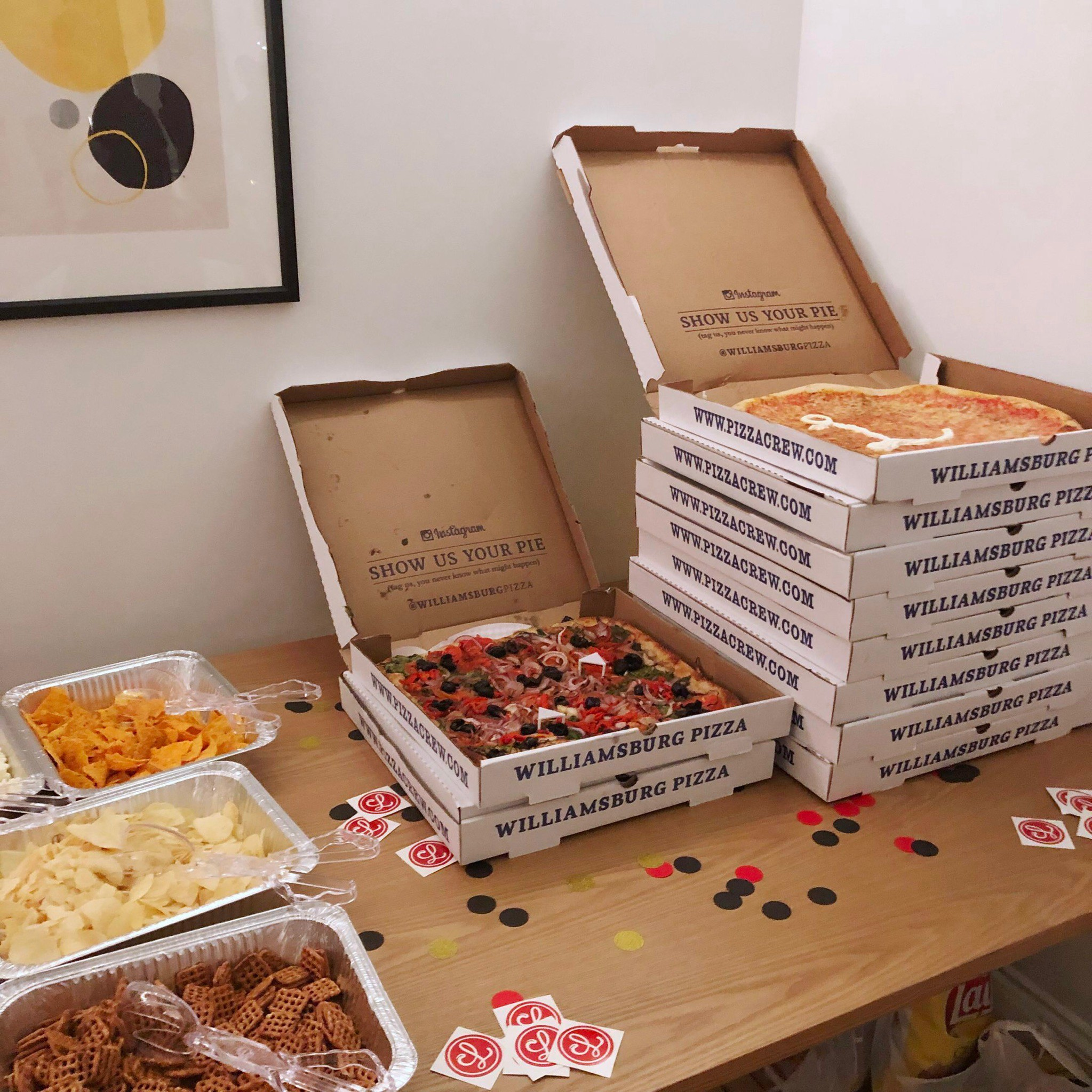 Boxes of pizza sitting on a table next to some snacks.