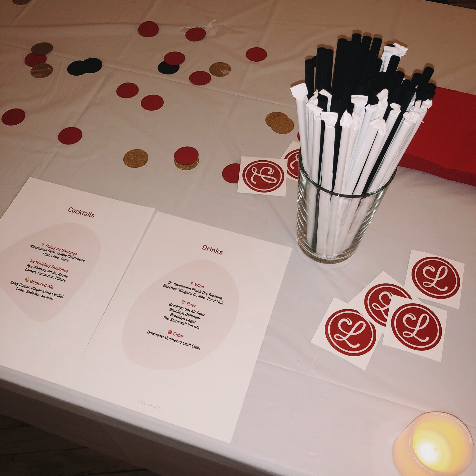 Cocktail menus sitting on a table decorated with stickers and confetti.