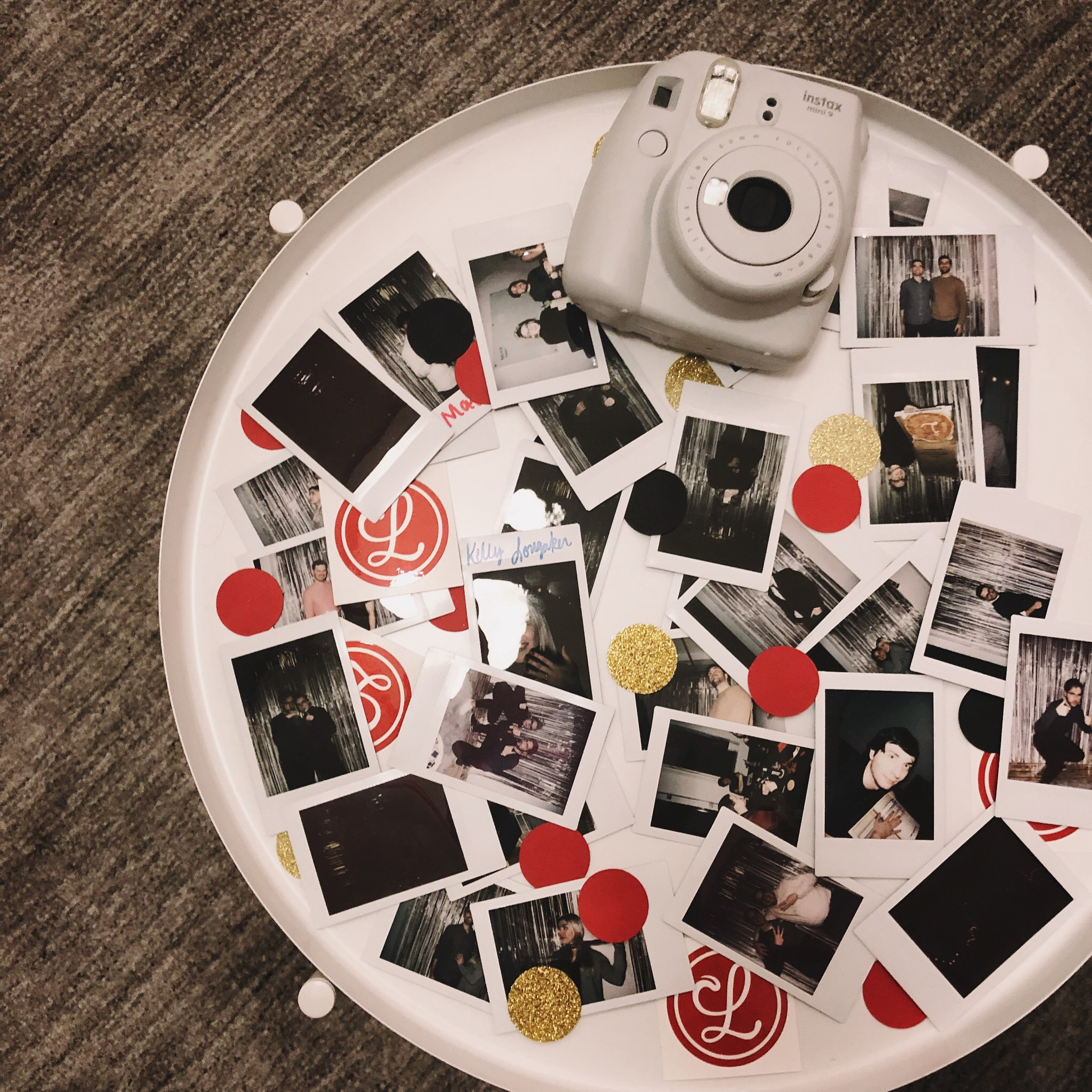 A bunch of instant photos sitting on a table with an Instax camera.